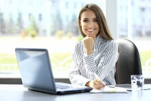 Woman smiling at her desk with her laptop