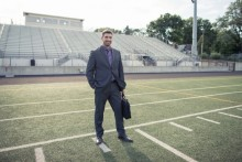 business man standing on a football field
