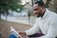 man reading book in the park, liberal studies degree, liberal studies student
