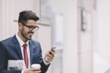 man walking out of the office with coffee on the phone