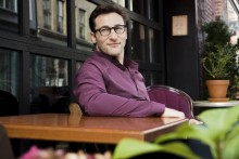 simon sinek sitting at a table