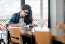 female student studying at desk, female student writing in book, college student studying at table, female student with glasses studying, female student taking notes at desk