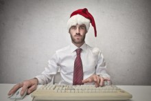 man in a santa hat working on a computer