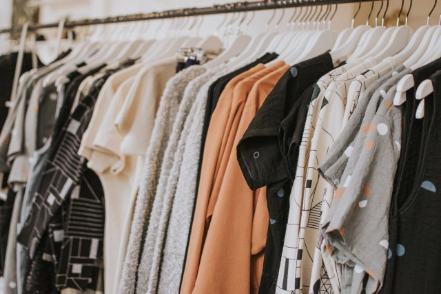 women's clothes hanging in shop, clothes hanging on a clothes rack, women's tops hanging on clothes rack, women's tops hanging on shirt rack