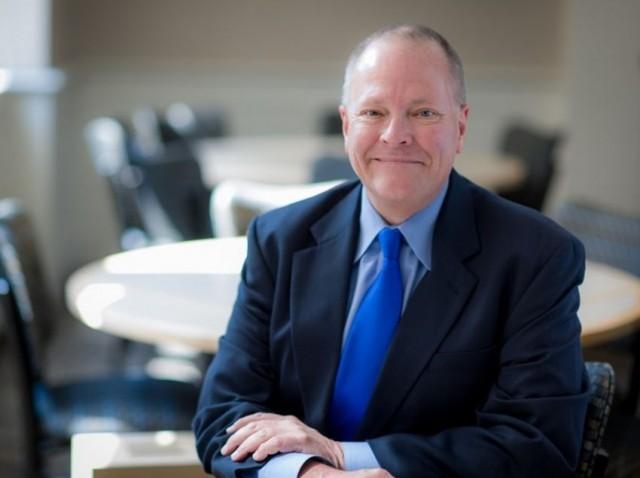 JWU Professor Rex Warren, Rex Warren, man in suit, man sitting at table, man sitting at table in suit with blue tie