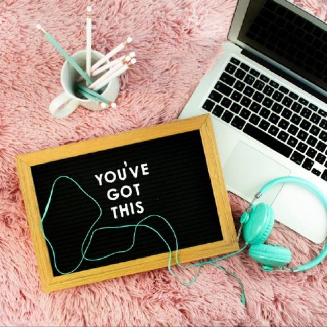 letter board with you've got this on it, apple laptop, turquoise headphones, mug with pencils, college student's room
