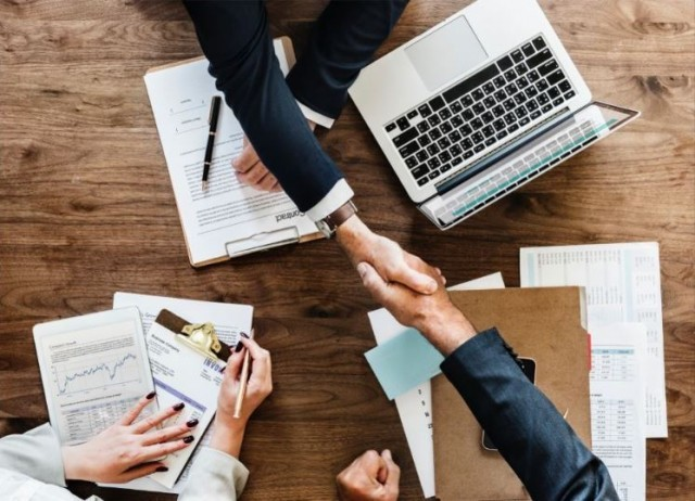 business people shaking hands, aerial view of business meeting at table, business meeting