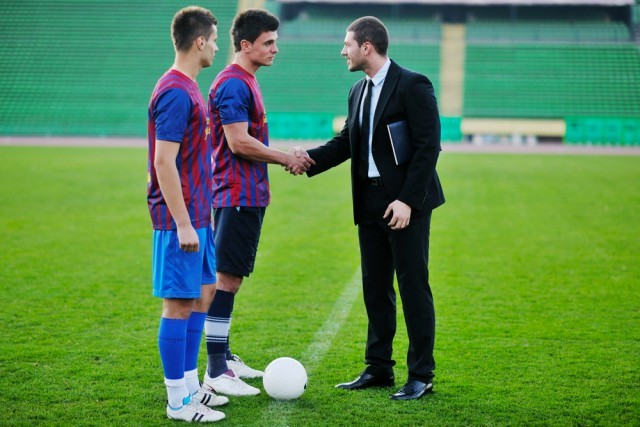 soccer manager on the field with two players