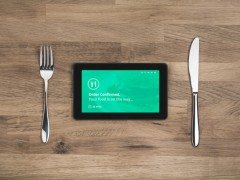 tablet on dinner table between fork and knife, tablet with words order confirmed your food is on the way, food order delivered via tablet