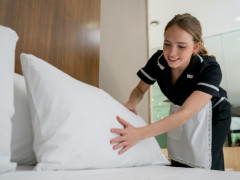 hotel housekeeper, housekeeper cleaning hotel room, housekeeper fluffing pillow, housekeeper making hotel bed, housekeeper making bed