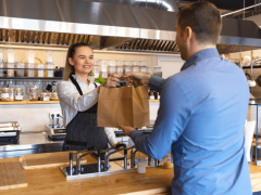 Woman handing man a takeout bag