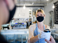 masked woman serving coffee