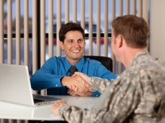 service member speaking with man at a desk