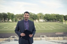 man in suit, man standing in bleachers with football field in background, business man in suit holding clipboard