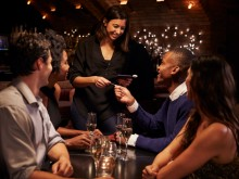 waitress at table of four, man giving credit card to waitress, dinner at nice restaurant, waitress serving table of four at dinner
