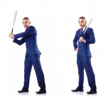 Businessman swinging a bat