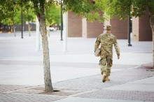 military man walking across campus