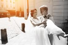 groom carrying his bride in her wedding dress